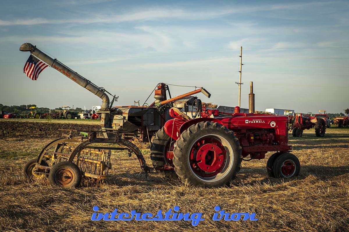 Farmall M with a hay rake.