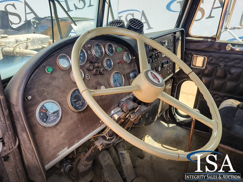 Driver's side interior, dashboard, and steering wheel of a Peterbilt 359 day cab